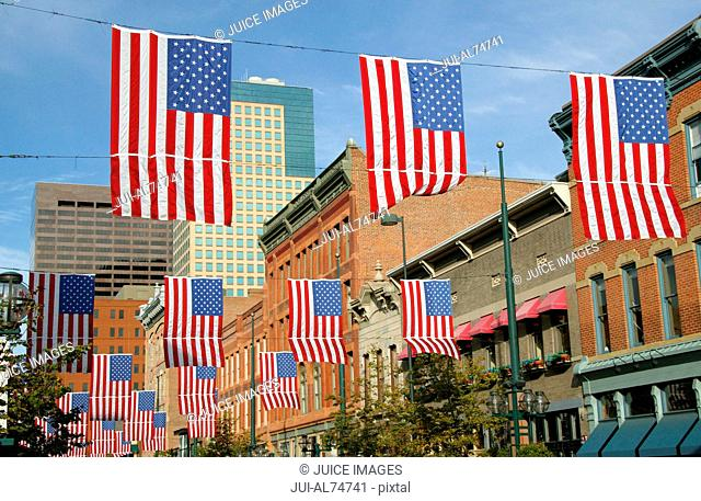 View of American flags hanging between buildings in Larimer Street, Denver, Colorado, USA