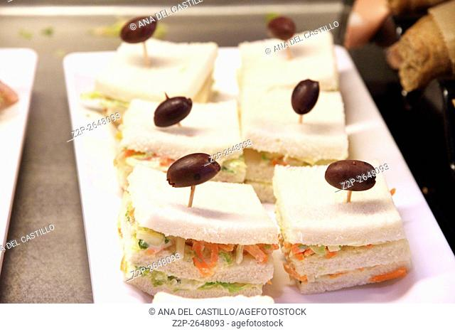 Salad sandwiches with black olive on top