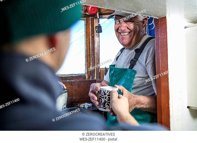 Fisherman getting cup of coffee