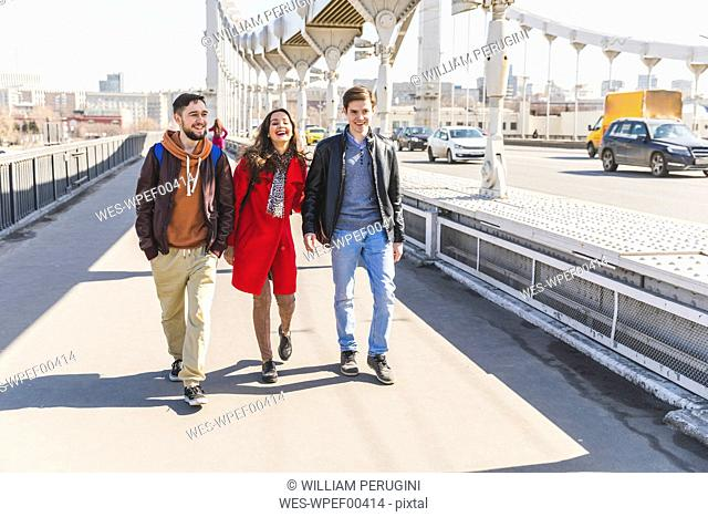 Russia, Moscow, group of friends walking over a bridge