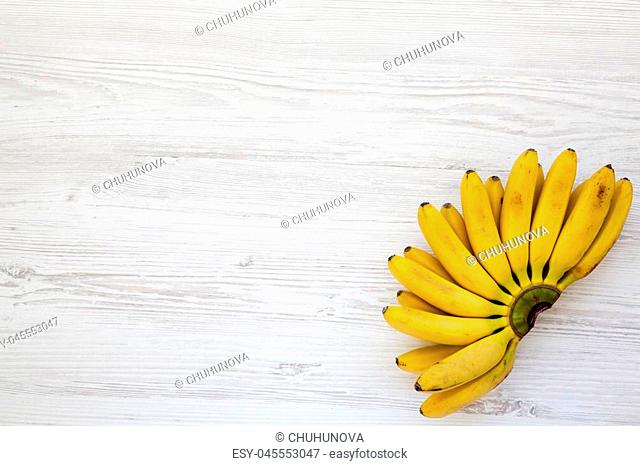 Bunch of baby banana on white wooden background, top view. Space for text