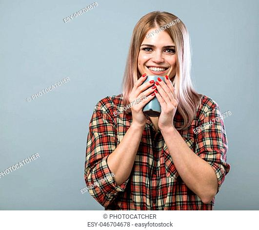 Young cheerful woman with smile hold mug with coffee or tea