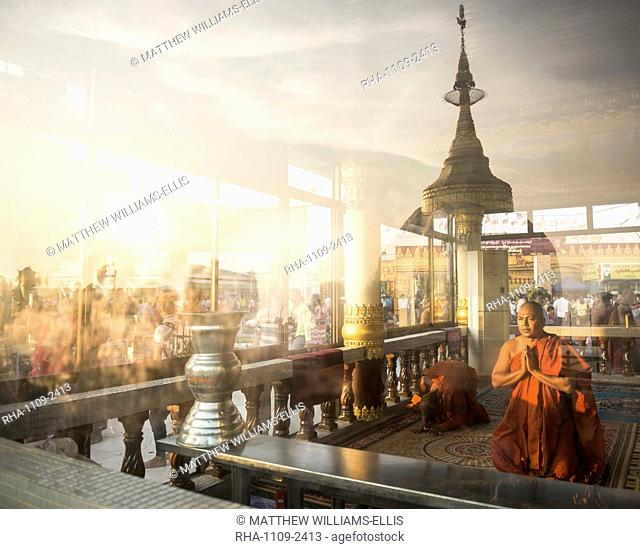 Buddhist Monks praying at Golden Rock Temple (Kyaiktiyo Pagoda) at sunset, Mon State, Myanmar (Burma), Asia