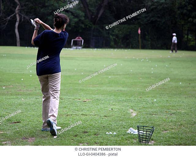 Young woman practicing golf, New Delhi, India