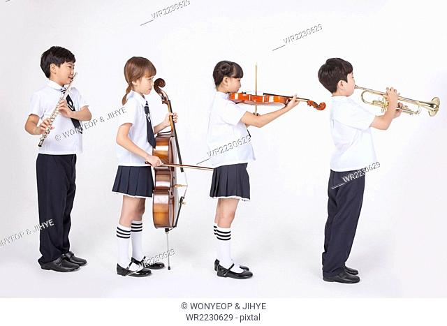 Four elementary school students in school uniforms standing in line and playing a classical musical instrument each
