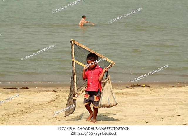 A child carrying his father's net & bag after his father back from fishing in sea