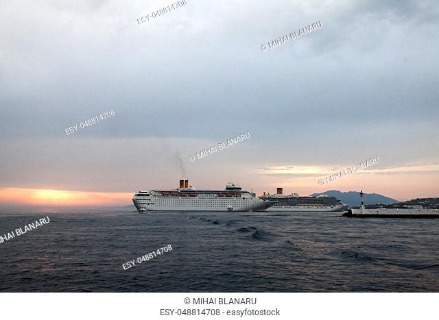 Sunset in Mikonos with a large boat next to a bridge