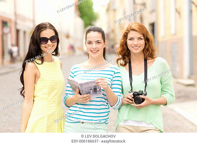 tourism, travel, leisure, holidays and friendship concept - smiling teenage girls with city guide and camera outdoors