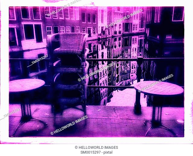 Pink tint of closed cafe terrace next to canal, Amsterdam, Netherlands