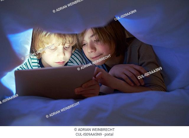 Brothers underneath duvet using digital tablet
