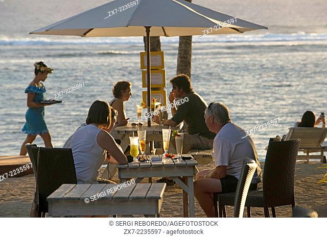 Rarotonga Island. Cook Island. Polynesia. South Pacific Ocean. Tourists photographing the sea and enjoying the sunset on the beach of the Hotel Crown Beach...