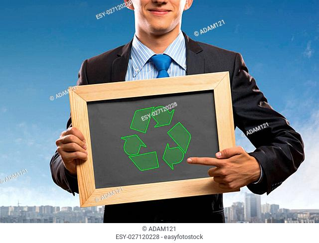 Close up of businessman holding chalkboard with recycle sign