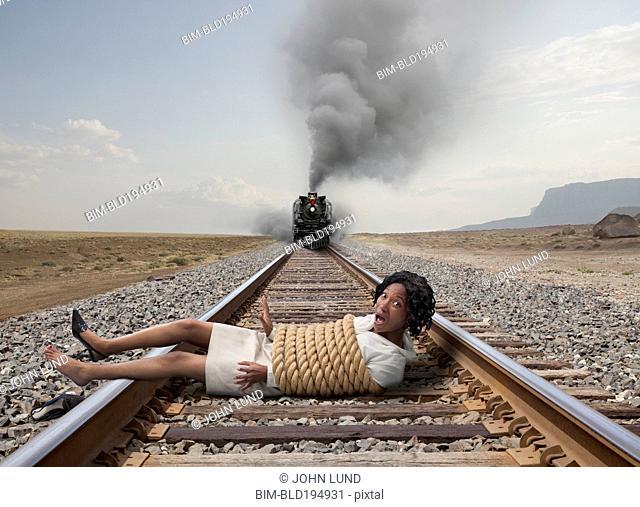 Black businesswoman tied to train tracks