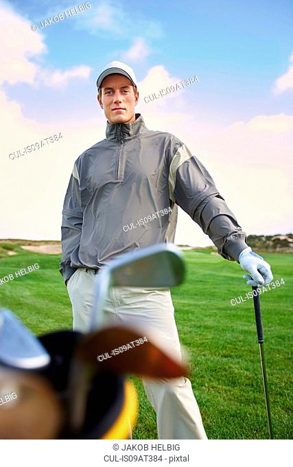 Golfer holding gold club, hand in pocket, looking at camera