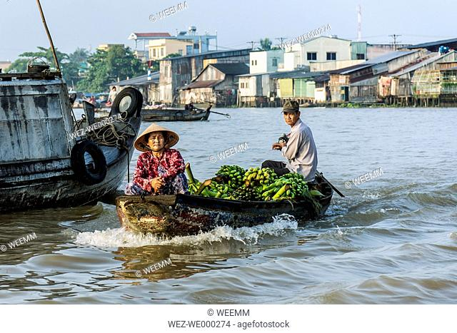 Vietnam, view to couple selling bananas at floating market