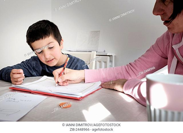 Learning at home-private tutor helps boy with homework,UK