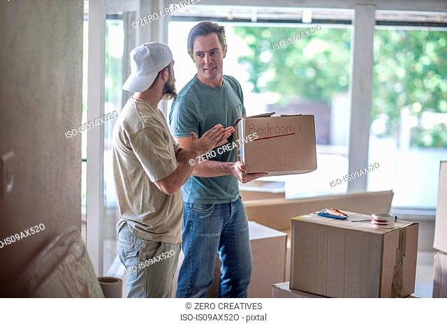 Moving house: two men talking in room filled with cardboard boxes