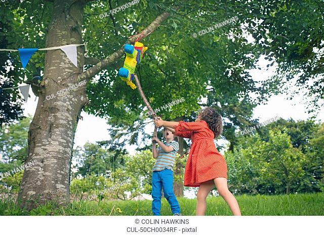 Children swinging at pinata at party