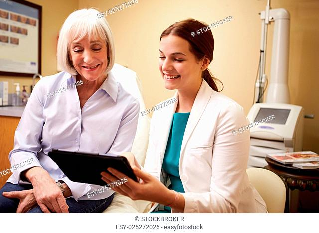 Cosmetic Surgeon Discussing Proceedure With Client In Office
