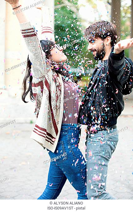 Young couple throwing confetti over each other in park, Brooklyn, New York, USA
