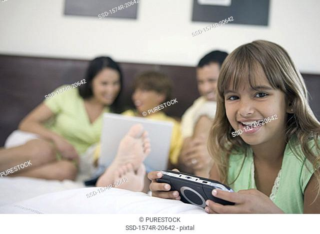 Portrait of a girl holding a handheld video game with her parents and brother looking at a laptop in the background