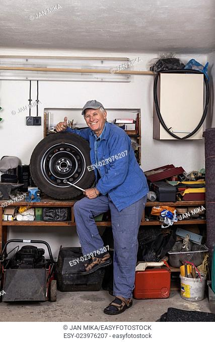 Portrait of happy senior worker with a tire and tool showing thumb up in the garage