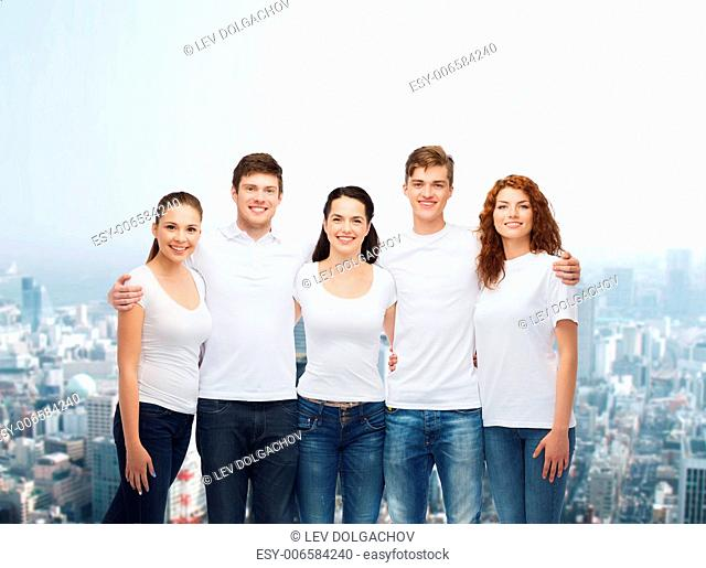 advertising, friendship, and people concept - group of smiling teenagers in white blank t-shirts over city background