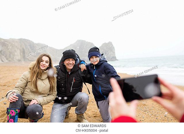 Happy family posing for photograph on snowy winter beach