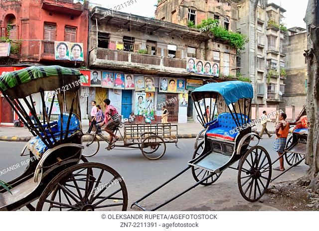 Rickshaw backs against the house with Indian political posters, Kolkata, India