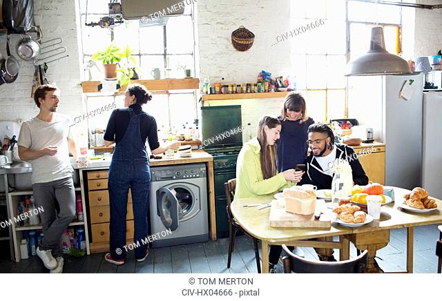 Young adult roommate friends enjoying breakfast in apartment kitchen