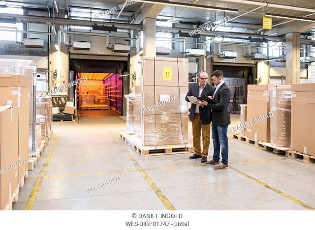 Two men talking in factory warehouse