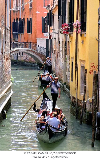 Gondolas and gondoliers in a canal, Venice, Veneto, Italy