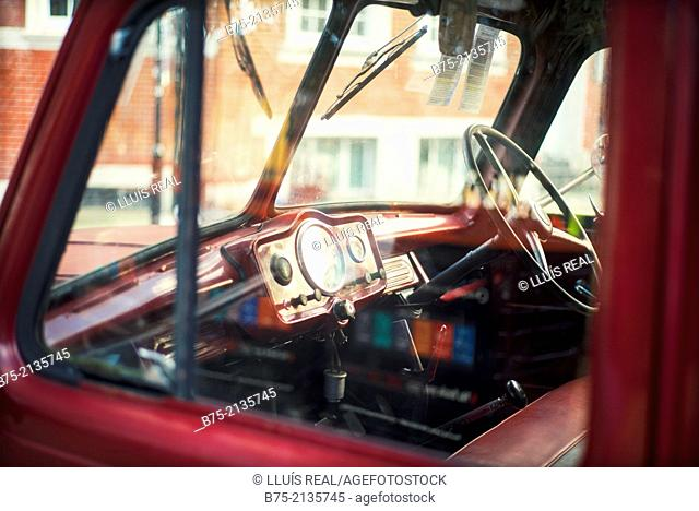 Dashboard of a vintage car seen through the window in a street in London, England, UK, Europe
