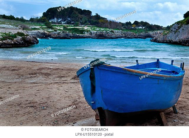 Beached blue wooden fishing boat on sandy shore of Porto Badisco inlet, with rocky shore line, blue sky, Salento, Puglia, Southern Italy