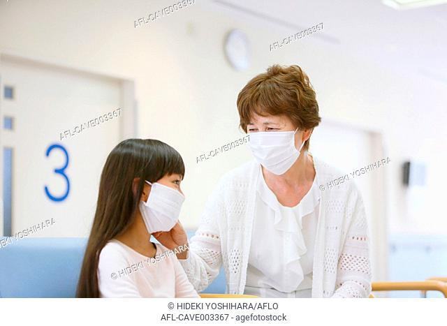 Sick young Japanese girl with grandmother at the hospital
