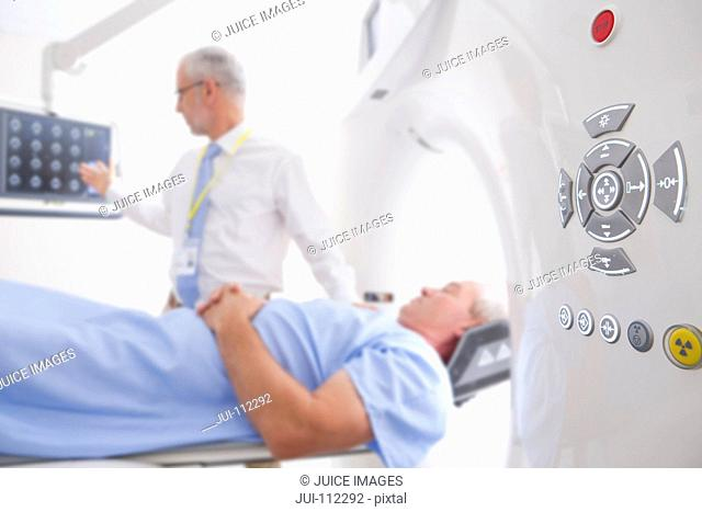 Doctor and patient reviewing digital brain scan at CT scanner in hospital