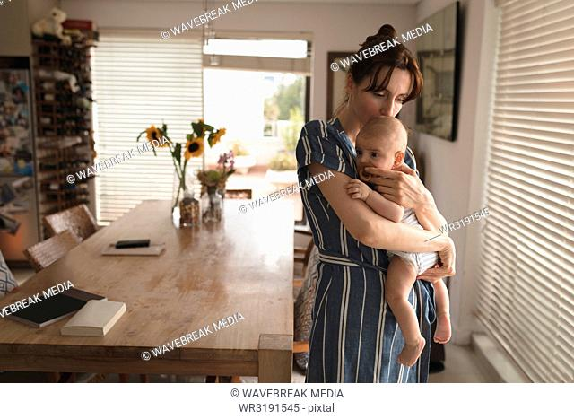 Young mom in bath rob holding and kissing her baby in living room