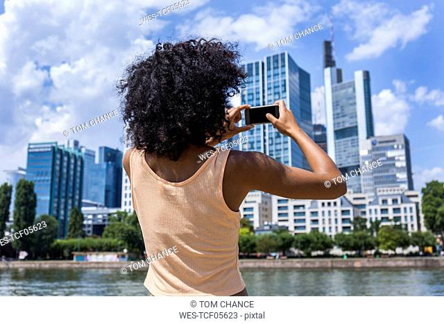 Germany, Frankfurt, back view of young woman with curly hair taking photo with smartphone