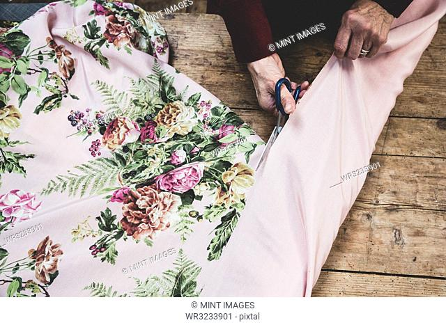 High angle close up of woman using scissors to cut pink fabric with floral pattern