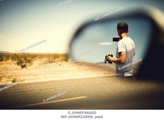 Man reflecting in side view mirror