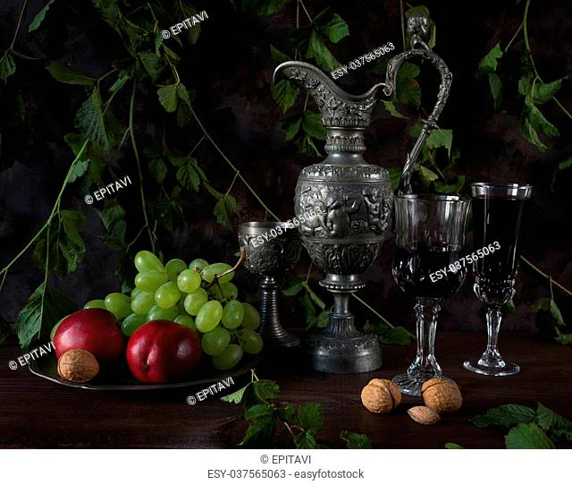 Still life in medieval style with antique pitcher and a goblets filled with red wine as well as walnuts, green grapes and nectarines on a dark background