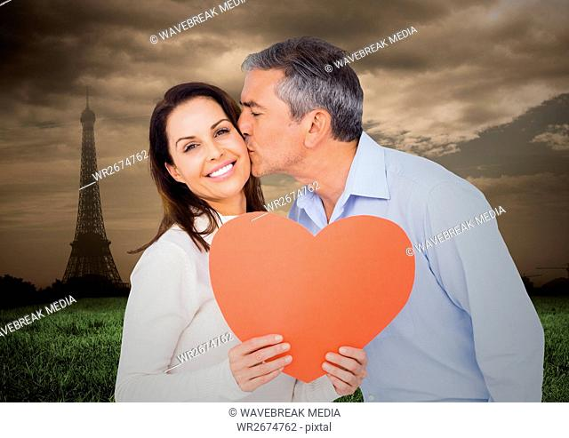 Romantic couple holding heart with eiffel tower in background