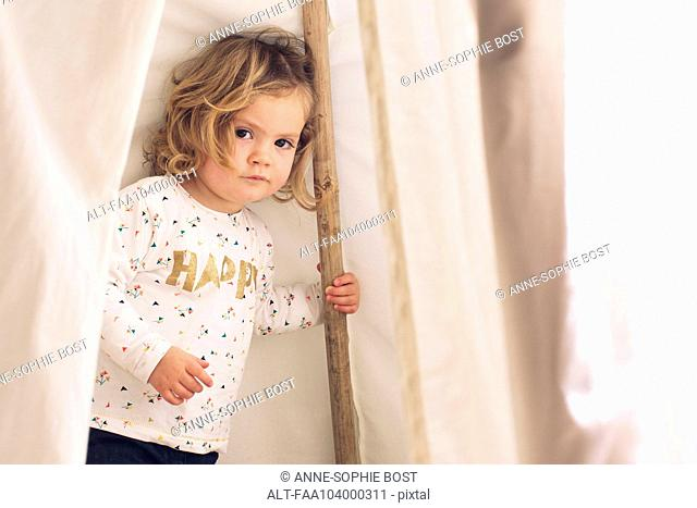 Little girl playing in tent, portrait