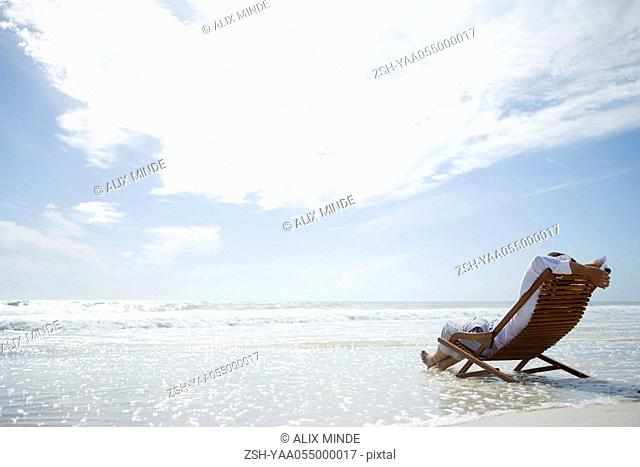 Man sitting in deckchair on beach, surf washing under him, rear view