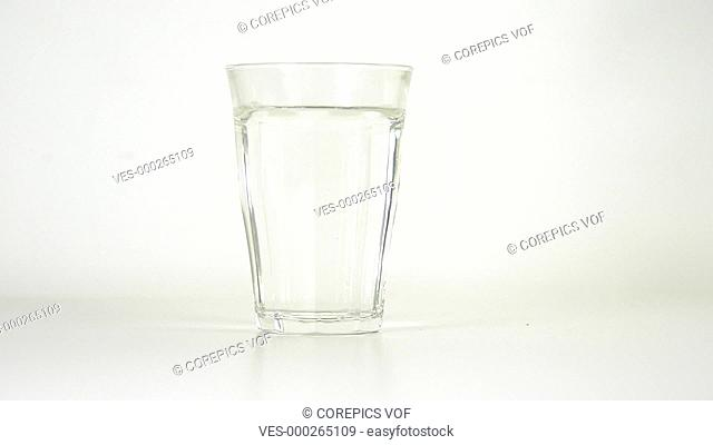 Vitamin effervescent tablet dissolving in a glass of water on a white background