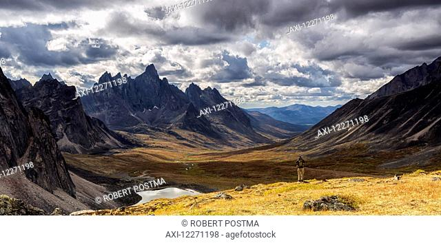 Hiker standing on an overlook taking photos of the colourful valleys in Tombstone Territorial Park in autumn; Yukon, Canada