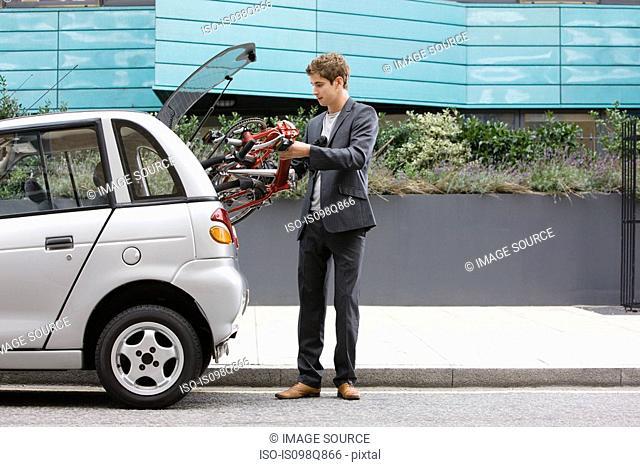 Man putting bicycle in car boot