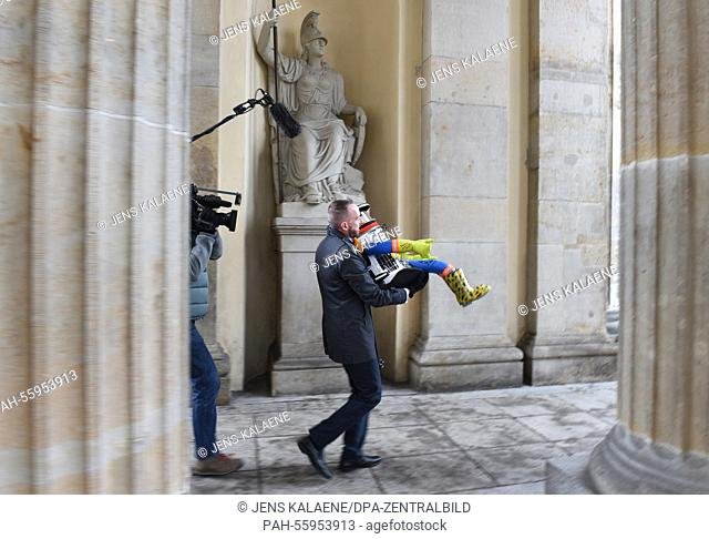 Ben MacLean of the Canadian embassy carries robot 'hitchBOT' through the Brandenburg Gate in Berlin, Germany, 18 February 2015