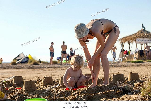 Croatia, Dalmatia, Mother And Son Playing On Beach