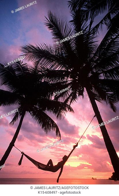 Sunset in hammock on tropical island beach